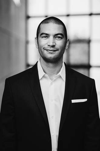 Black and white image of Matejka wearing light shirt and dark blazer.