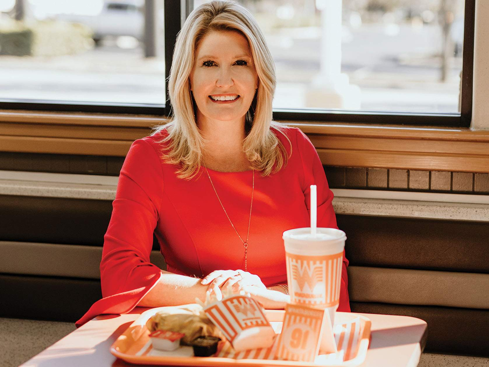 woman in red dress sitting at whataburger booth
