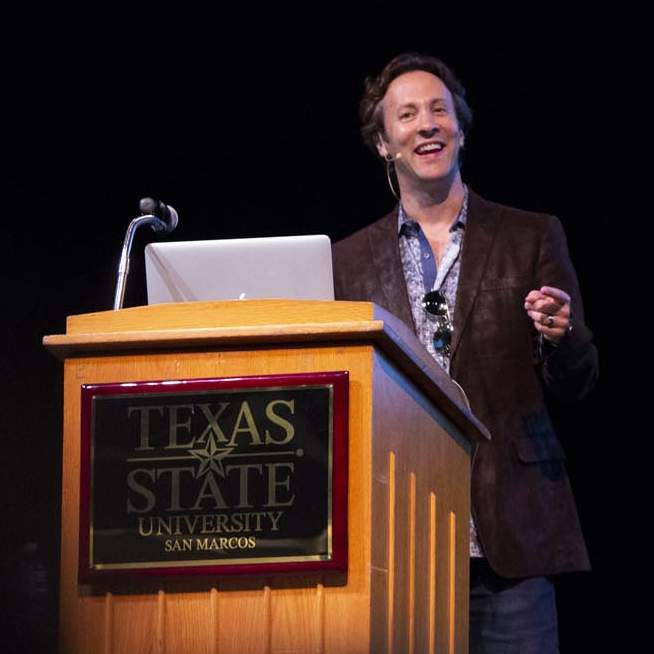 Dr. David Eagleman grinning at podium