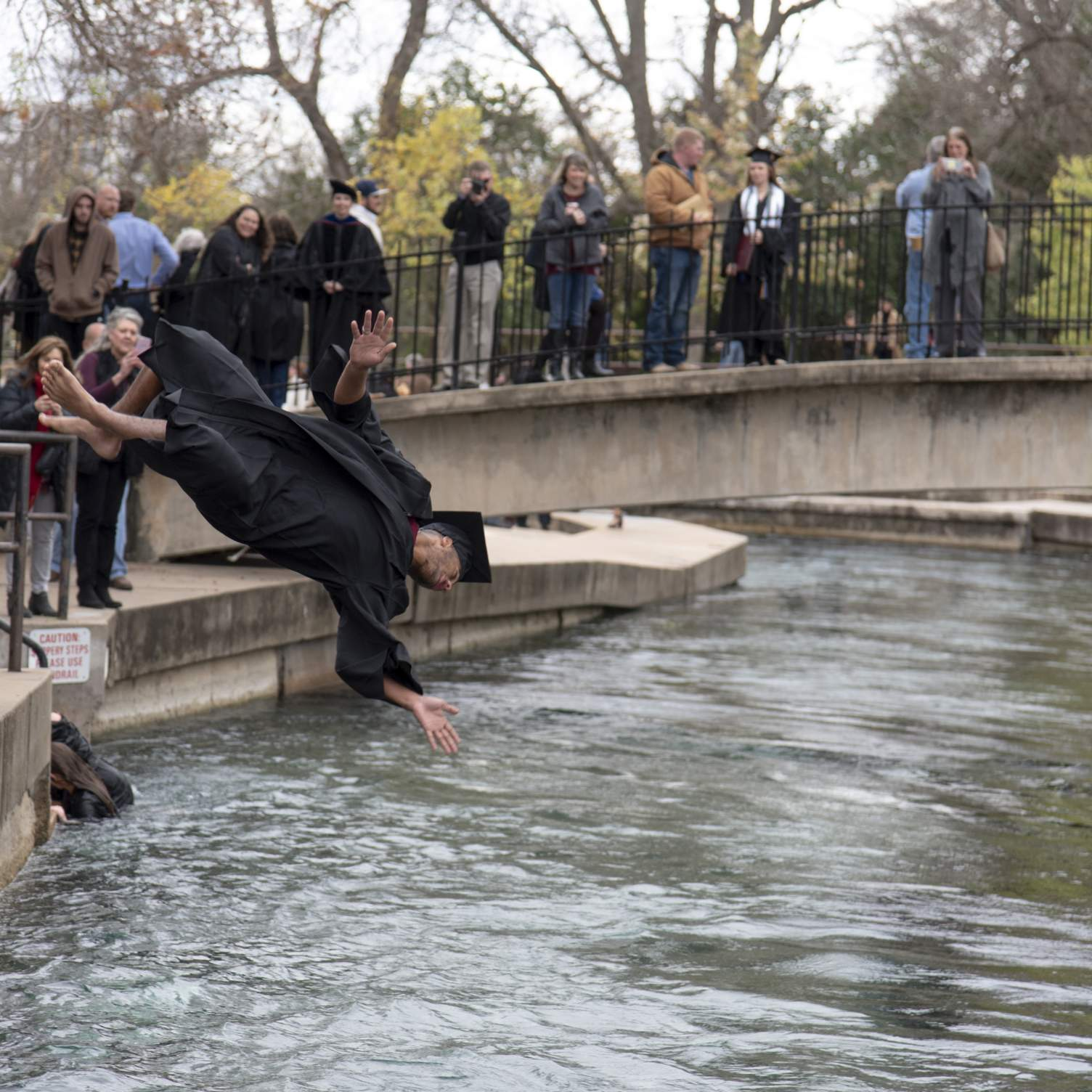 graduate doing backflip into San Marcos river in Sewell Park