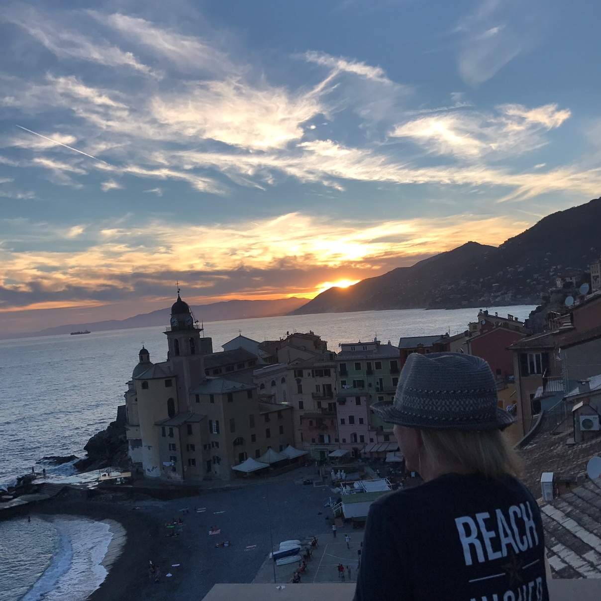 "Woman wearing a shirt that says ""reach higher"" look out at the sun setting"