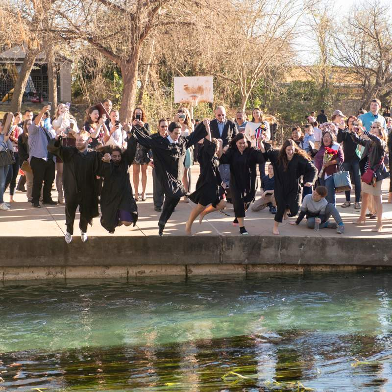 graduates jumping into Sewell Park river