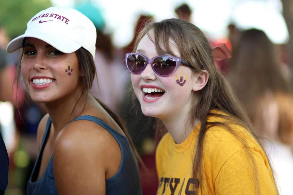 two female students laugh while wearing their texas state apparel