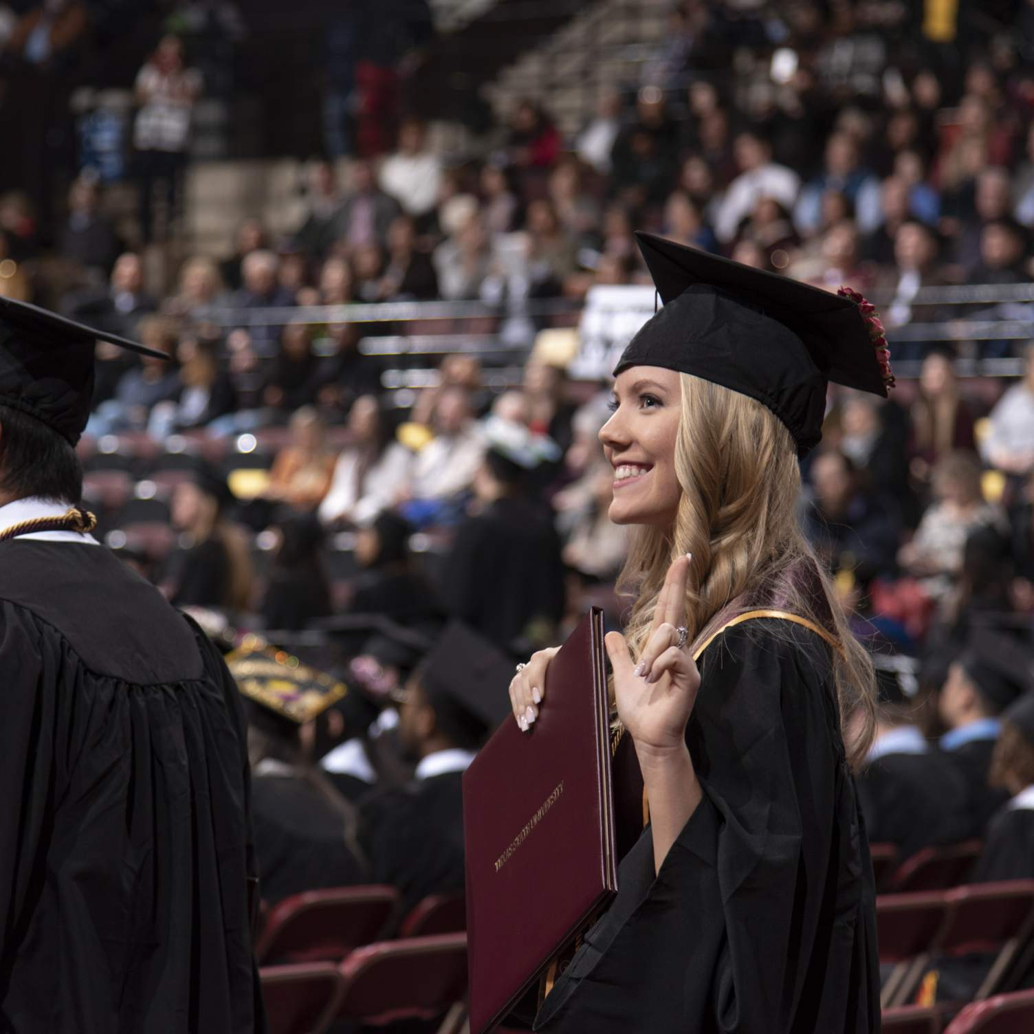graduate holding diploma and doing Texas State hand-sign