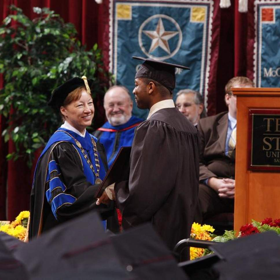 President Trauth shakes hands with graduating candidate