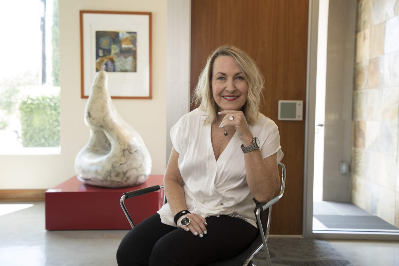 Donor, Leslie Fossler is seated in her office with a sclupture behind her