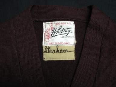 "Photograph of the inside label of the sweater with the name ""Strahan"" sewn inside."