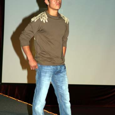 Student with long-sleeved shirt with a wing design on the shoulders, jeans and sneakers.