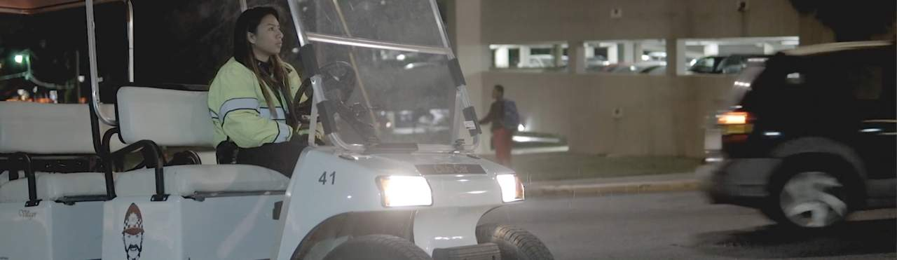 daisy diaz driving a bobcat bobby around campus at night