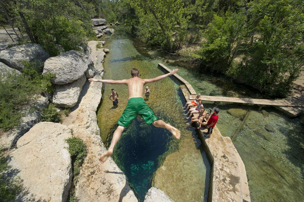 boy jumping into jacobs well