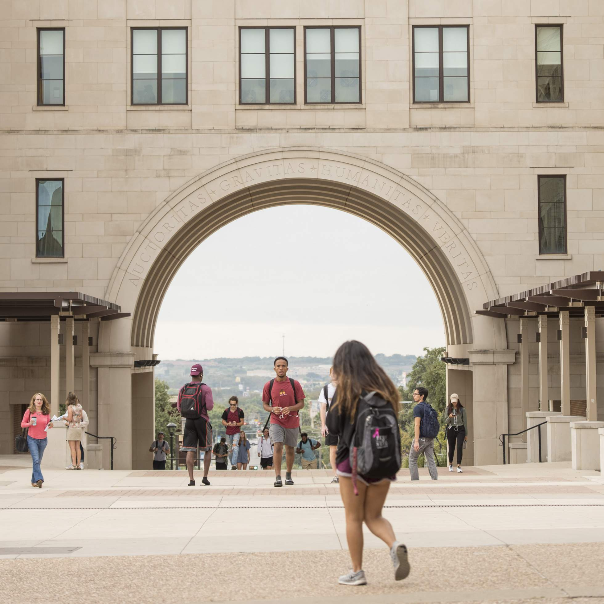 Students walking through the UAC arch.