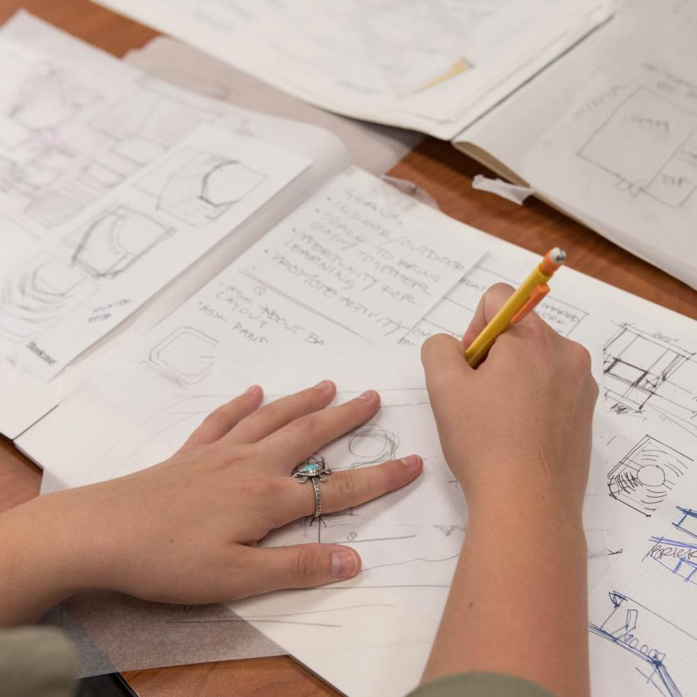 we see hands up close sketching out furniture designs