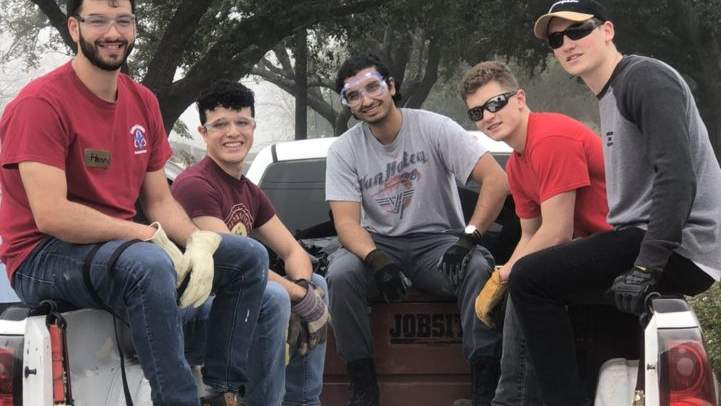 Bobcat Break Winter Trip attendees pose in the bed of a truck with other volunteers during service.