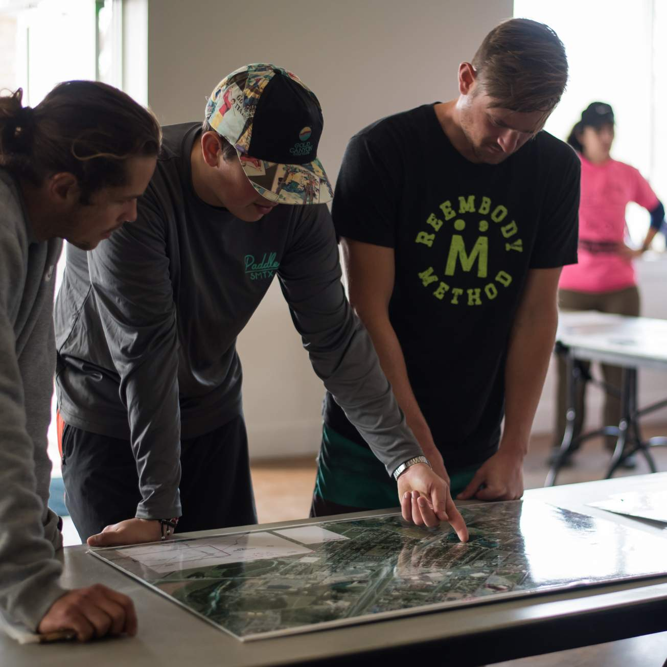 three San Marcos residents look at a map to plan out the river cleanup