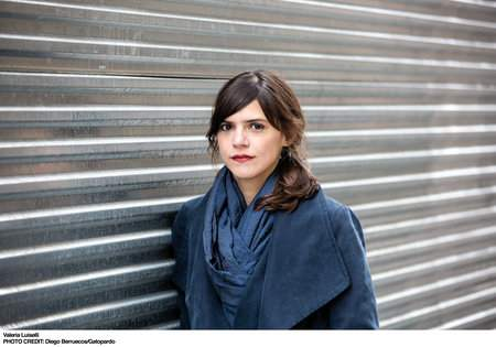 Valeria Luiselli, wearing blue, leans against a metal panel.