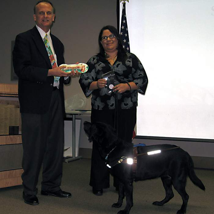 Bob Seese presents  the Isis de la O Gomez Student Award for Outstanding Achievement in International Education to Sasha Rangel with her guide dog, Glorianne.
