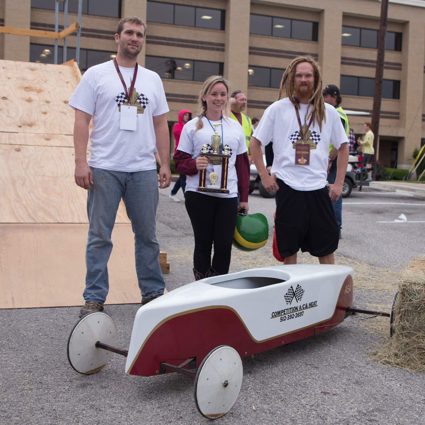 three contestants stand behind their car