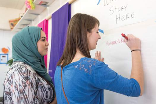 Female students writing on board in classroom