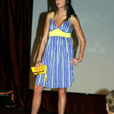 Student wearing a striped sundress with yellow straps trim at the high waist, carrying a yellow purse, and wearing yellow high heels.