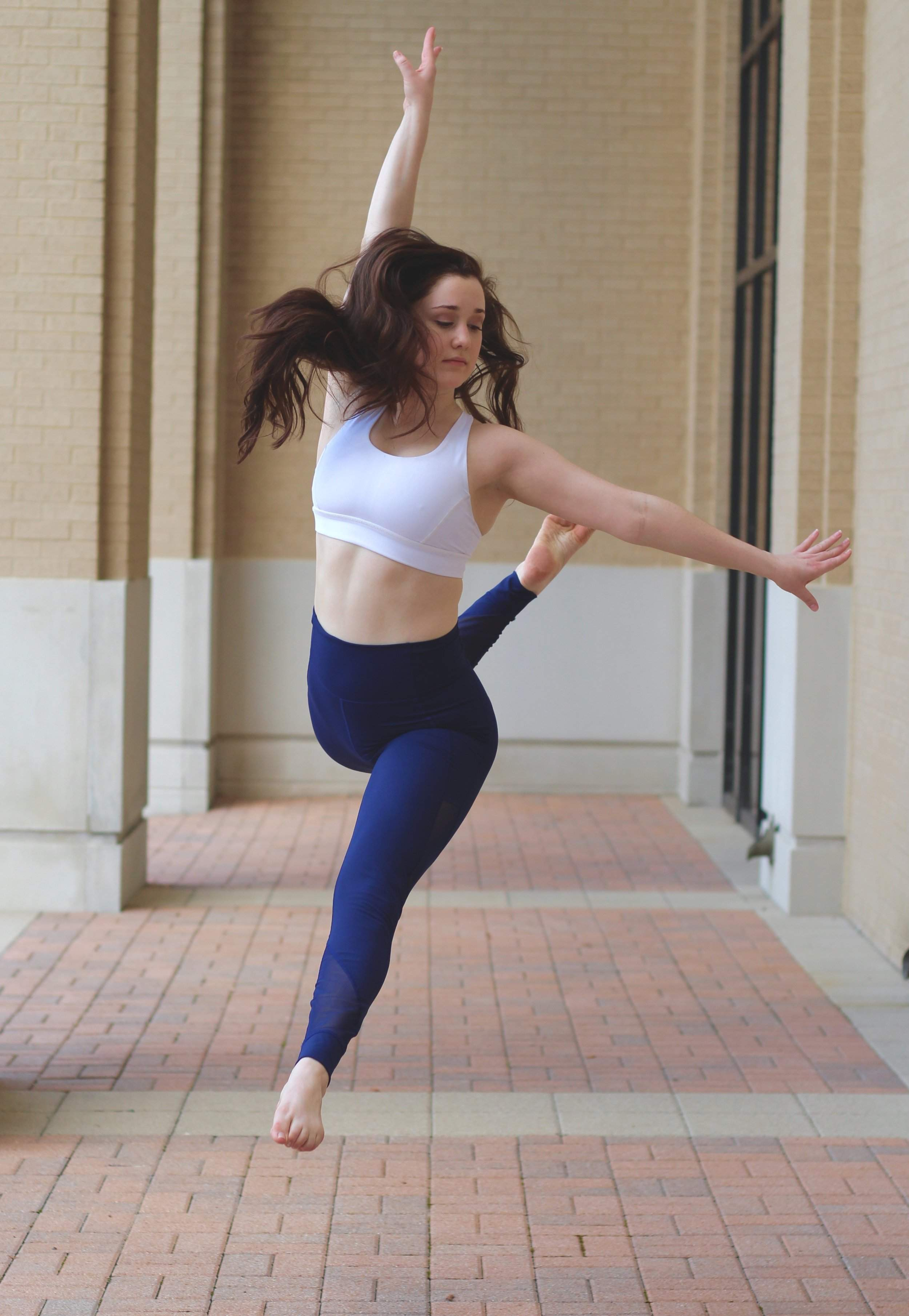 Alexandra leaping into the air in blue pants and white top
