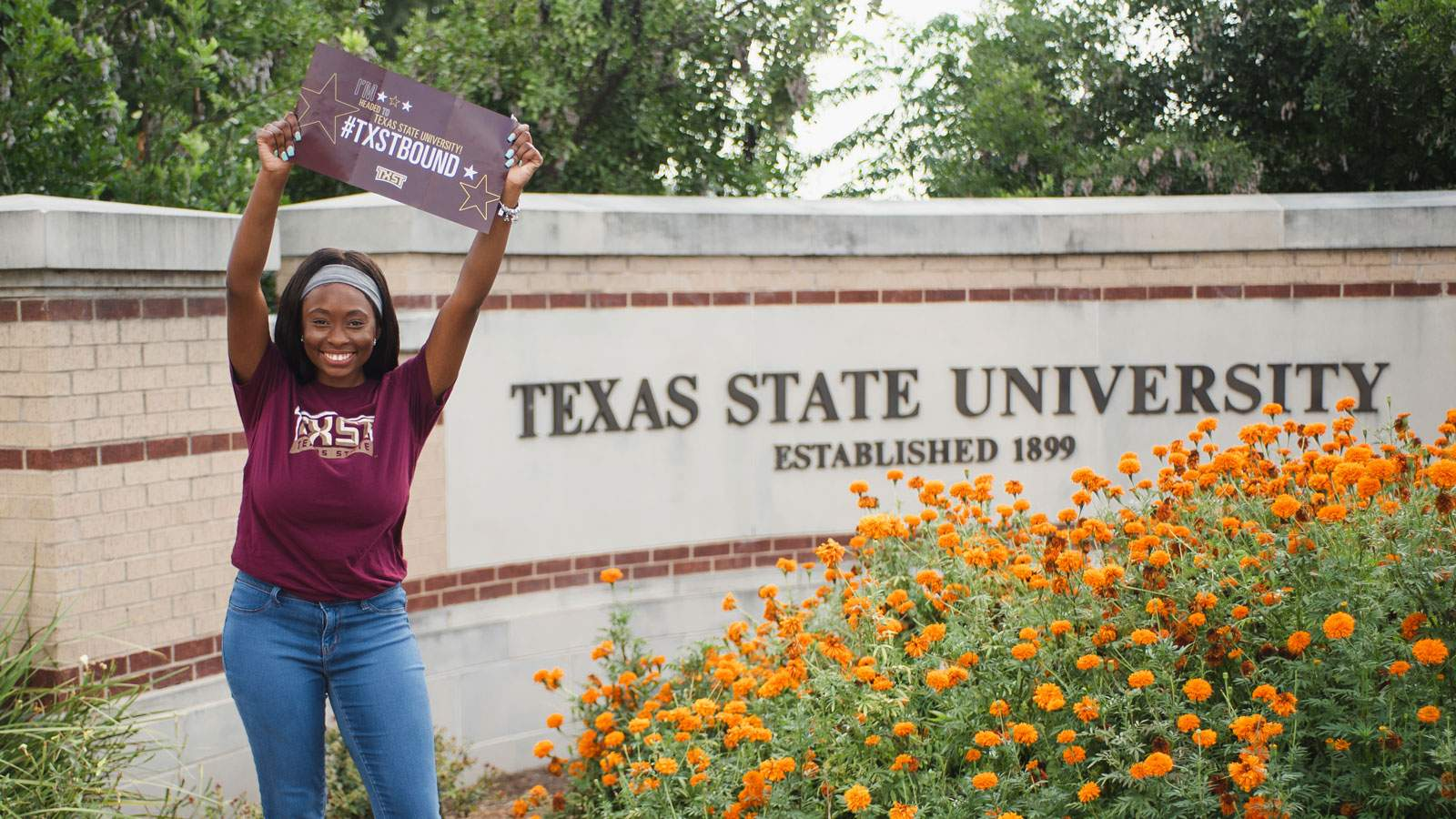 student poses with banner in front of TXST sign