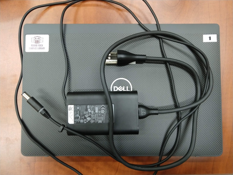 closed laptop with charger on top