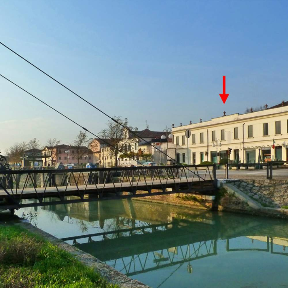 "This photograph shows the swinging bridge over the Brenta Canal in La Mira with the Villa Foscarini marked by a red arrow.  A plaque on the villa's wall reads LORD BYRON ABITO 1817 (""Lord Byron lived here in 1817"")."