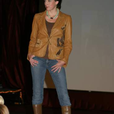 Student wearing brown leather jacket, jeans with knee-high boot over and bead necklace at the fashion show.