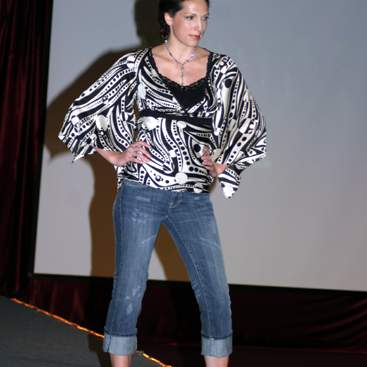 Student wearing a black & white flowing sleeve print shirt over a black tank-top, jeans and high-heels.