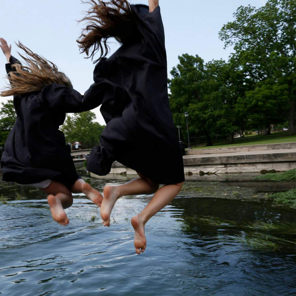 Graduates jump into the San Marcos River.
