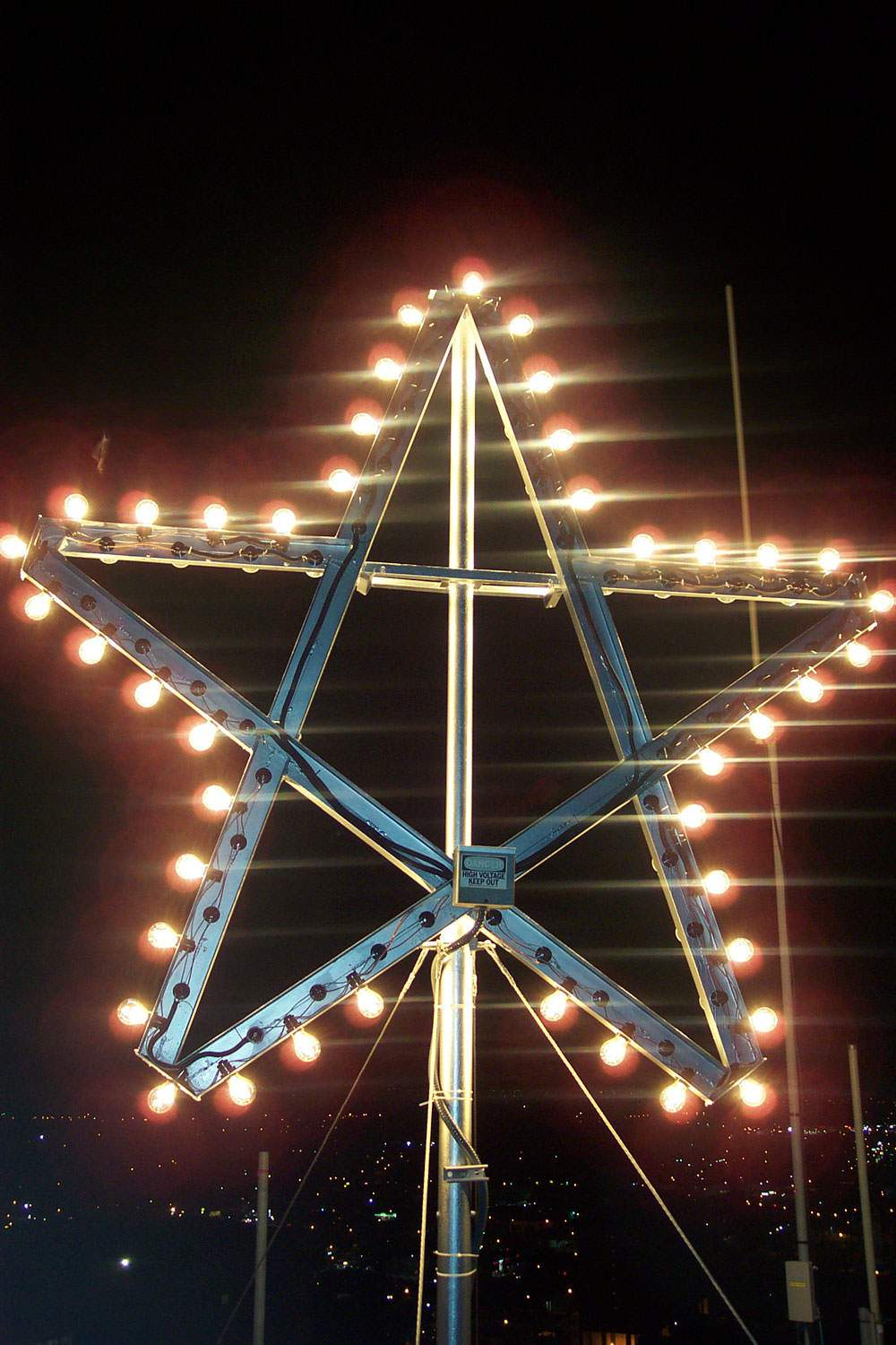 the victory star is lit up at night on the top of jackson hall