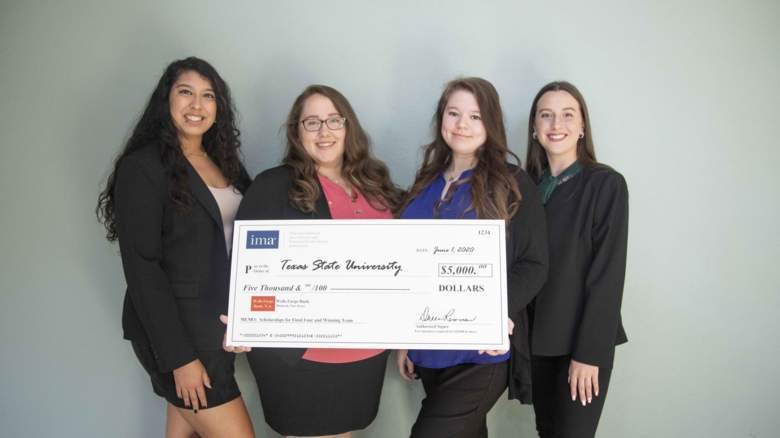 four accounting students holding oversize $5,000 check prize money from competition win