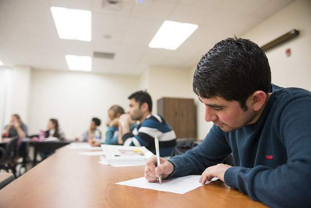 student at writing on paper