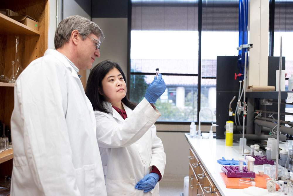A photo of a professor and a student looking at a vial in a laboratory.