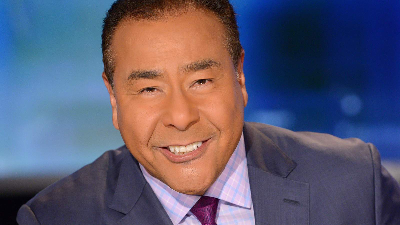 John Quiñones smiling on a TV news set