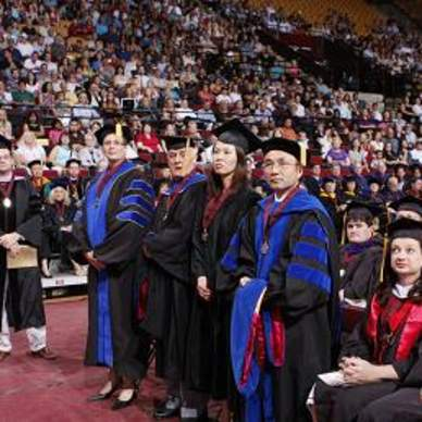 Doctoral candidates standing during ceremony