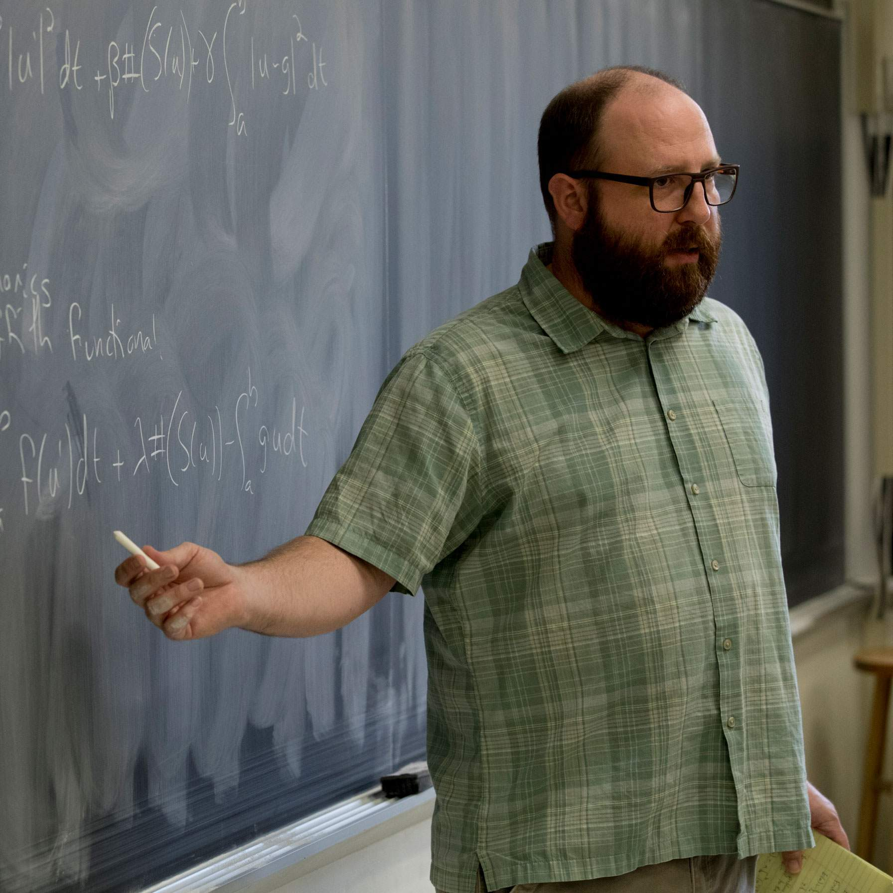 professor going over lesson at chalkboard