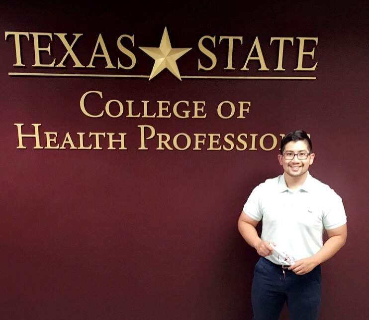 "Kevin Ambrocio stands in front of a sign that reads ""Texas State College of Health Professions"""